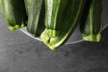 Bowl with fresh green zucchini on color background