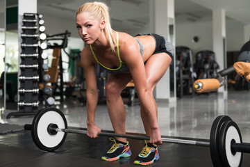 Fitness Woman Doing Exercise For Back With Barbell