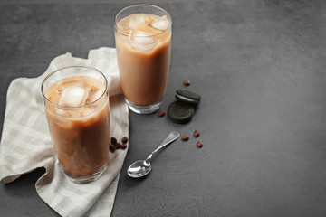 Iced coffee with milk in glasses on grey background
