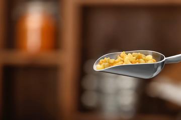 Pasta in metal scoop on blurred background