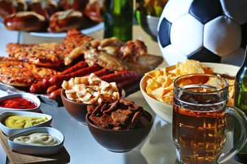 Ball, beer and tasty snacks on kitchen table, close up view