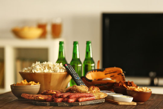 Tasty snacks, beer and baseball glove on kitchen table against blurred background