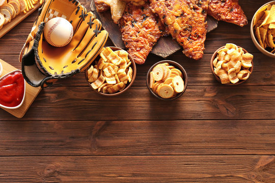Baseball glove, ball and tasty snacks on wooden table