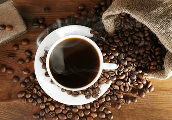 Cup of fresh coffee and sack with beans on wooden background, top view