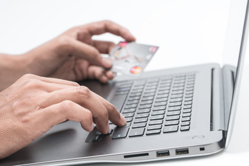 Man's hands holding a credit card and using pc or laptop for onl