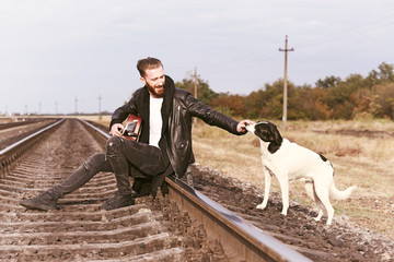 Handsome man with guitar and cute dog on railroad