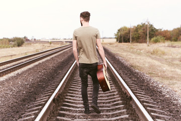 Handsome man with guitar on railroad
