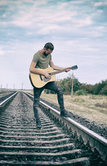 Handsome man playing guitar on railroad