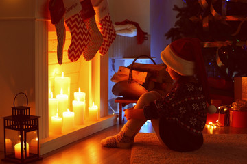 Little girl sitting near fireplace decorated for Christmas