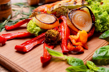 Grilled vegetables on wooden cutting board, closeup