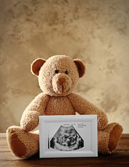 Teddy bear holding photo frame with ultrasound picture of baby on table