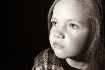 Portrait of cute little girl on black background