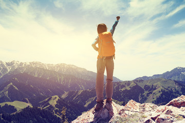 cheering young woman hiker at mountain top