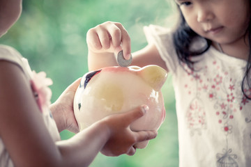 Child asian little girl putting coin into Piggy Bank in vintage