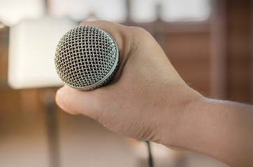 Close-up of handle microphone in concert hall or conference room
