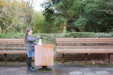 ゴミ箱にゴミを捨てる女の子