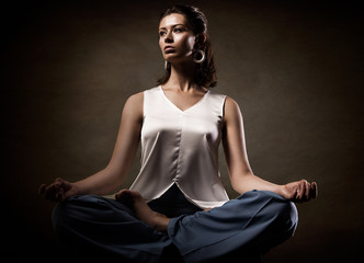 Stylish young athletic girl in fashionable clothes, showing yoga asanas in the studio. Beauty face and body health
