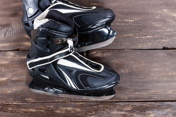 Overhead view of hockey ice skates on old rustic wooden table.