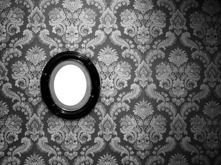Black and white of oval wall picture frame on classic wallpaper