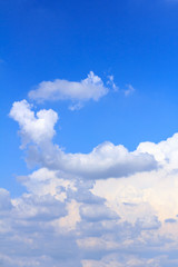 Blue sky background with white clouds and rain clouds.