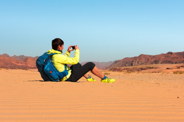 Woman Hiker with backpack makes photo in desert