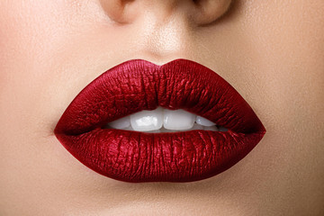 Close up view of beautiful woman lips with red matt lipstick