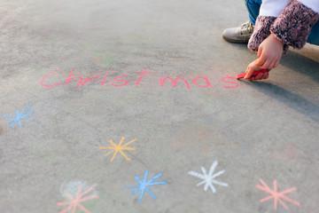 Child writing Christmas on the playground
