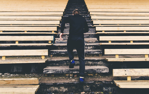 Man in sport clothes running climbing stairs in the stadium