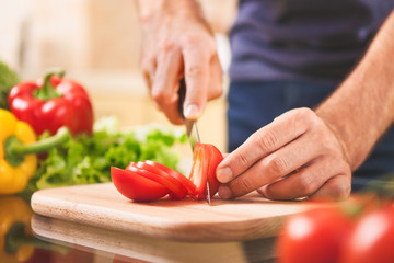 close up of male hand cutting tomato on cutting board
