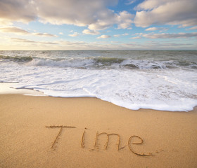 Time word on the sea sand.