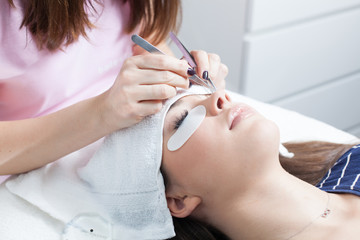 beautician making artificial lashes. eyelash extension procedure