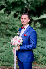 handsome and young groom in blue suit standing outdoors