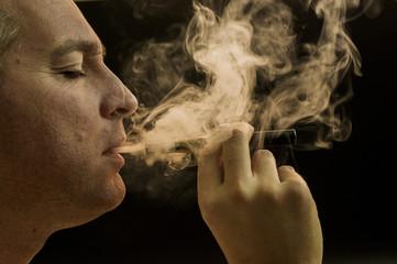 Man smoking cigarette on black background, Handsome young man smoking