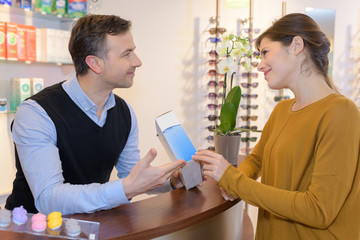 paying eye or sunglasses at optician store