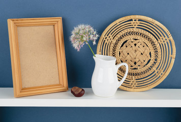 photoframe and vase with a flower on white  shelf on blue wallpa