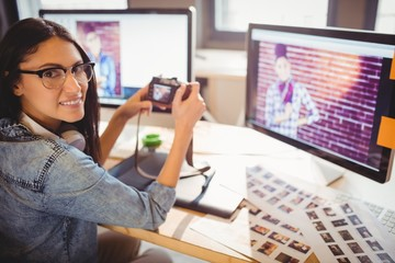 Graphic designer looking at pictures in digital camera