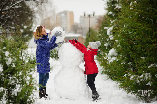 Mother with daughter of younger school age build a snowman in the park.