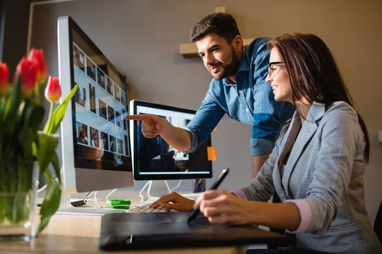 Graphic designer pointing at monitor