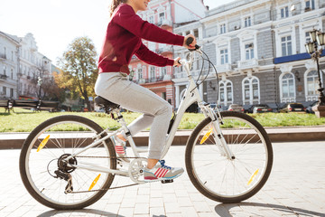 Cropped photo of young woman walking with her bicycle