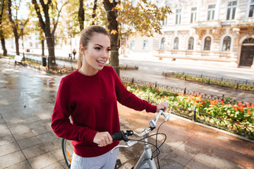 Young beautiful caucasian lady walking with bicycle in city