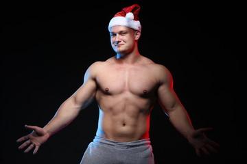 portrait of an athlete bodybuilder posing in cap Santa Claus on a black background