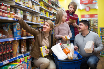 Happy family of four purchasing food together