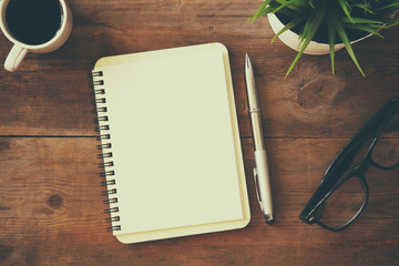 open notebook with blank pages next to cup of coffee