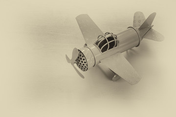 image of retro metal toy airplane over wooden table