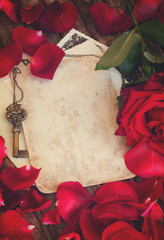 vintage background with red rose petals and gold key, retro toned