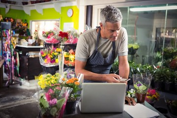 Male florist using mobile phone
