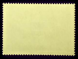 Posted stamp reverse  side with the edge of the sheet. Texture of paper.Isolated  on black background
