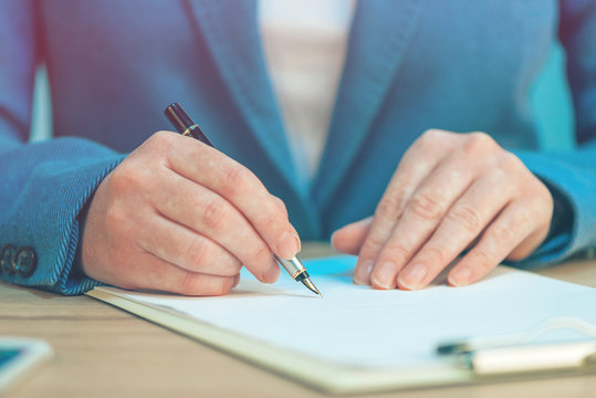 Close up of female hands writing signature on business agreement