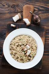 Above view of risotto with cep boletus, rustic wooden setting
