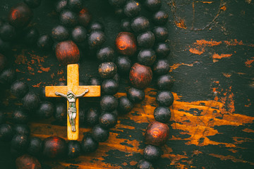 Catholic rosary prayer with a cross on old black wooden background with space for text. close-up, top view. tinted photo